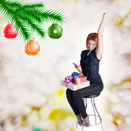 Happy red-haired girl with gifts and phone on a chair Holidays Christmas and New Year photo