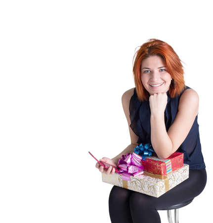 Happy red-haired woman with a gift box and a telephone on the white background photo