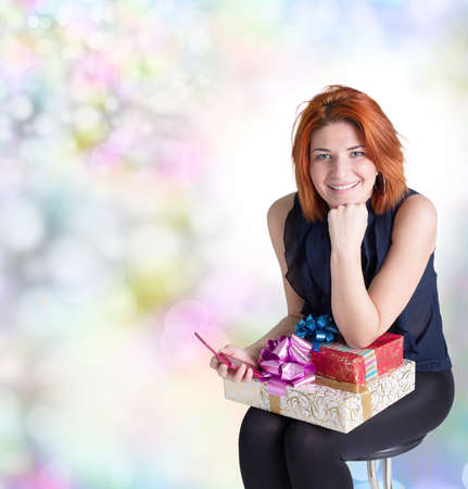 Happy red-haired woman with a gift box and a telephone on the abstract festive background photo
