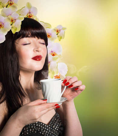 Beautiful girl with a cup of green tea buds of orchids photo