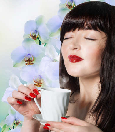 Beautiful girl with a cup of green tea buds of orchids Best tradition Tea photo