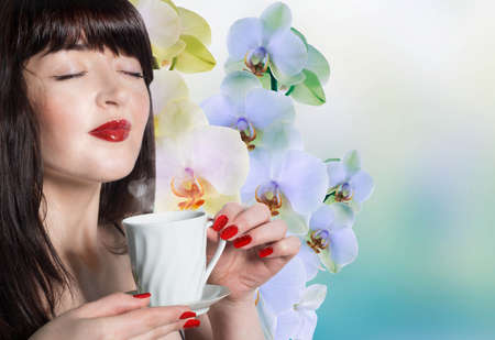 Beautiful girl with a cup of green tea buds of orchids Fresh aroma Tea photo