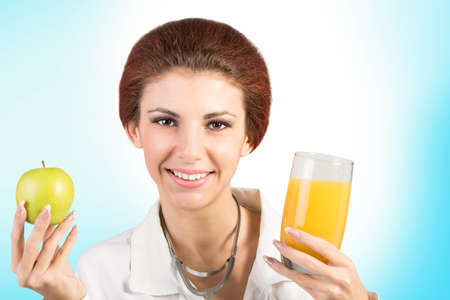 Beautiful Woman Doctor with Juice Orange Glass and Fresh Green Apple Healthy Food photo