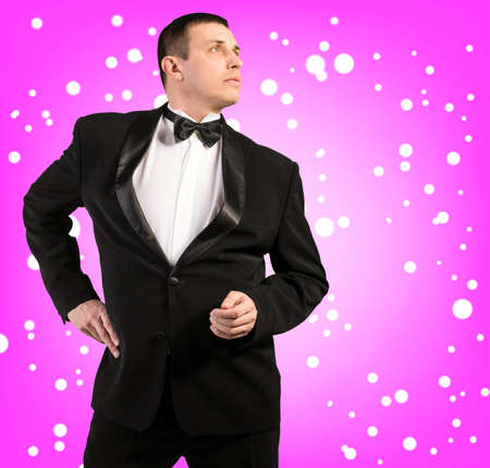 Portrait the Man in a classical tuxedo on an snow abstract pink background photo