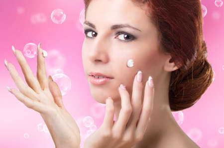 Beauty Girl Portrait  Beautiful Spa Woman Touching her Face Natural Cream for Skin Face photo