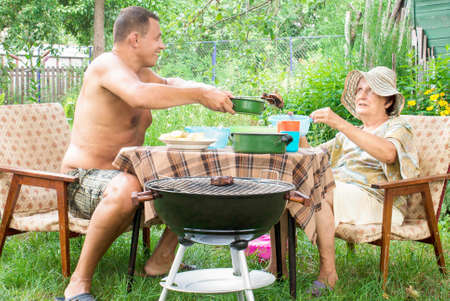 Happy family eating a barbecue in summer garden Lifestyle photo
