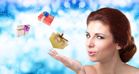 christmas perfume: Beautiful Women with flying gifts over abstract Christmas snow background Stock Photo
