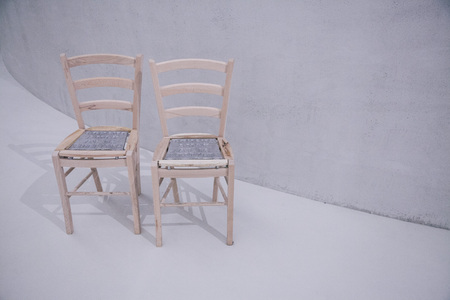 two chairs in front of white wall