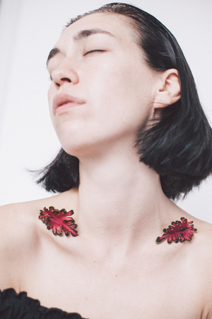 portrait of girl with closed eyes and leaves on shoulders