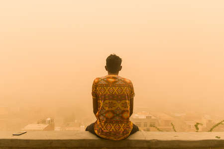 man sitting on the wall facing city enjoying the view in the middle of the sandstorm