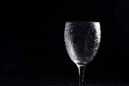 Wine glass in black and white on a black surrface with reflection and water drops