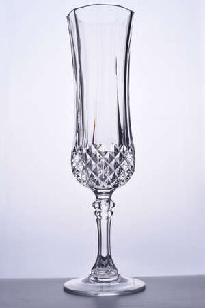 Glass goblet with space for text on a gray background. One wine glass on a gray background. One transparent glass for chompian on a white background