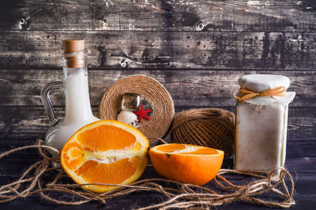 The lay composition with body care products and space for text on dark wood background. a jar of natural cream, a bottle of coconut oil and a ripe orange
