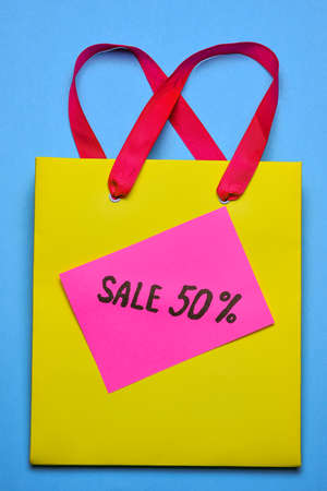 Yellow shopping bag with a sticker that says 50% discount on a bright blue background. Sale 50% off. Black friday or christmas sale concept