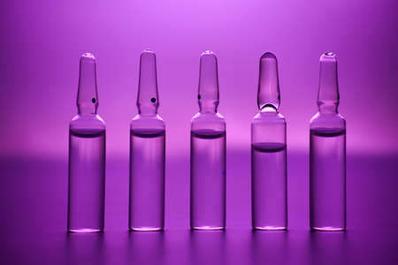 glass ampoules with liquid medicine in pink light