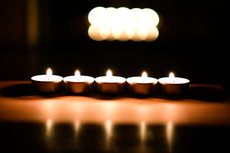 Close up of burning candles on the wooden table with blurred Christmas light background Stock Photo