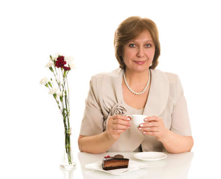 50 to 60 years: Old woman drinks coffee, isolated on white background
