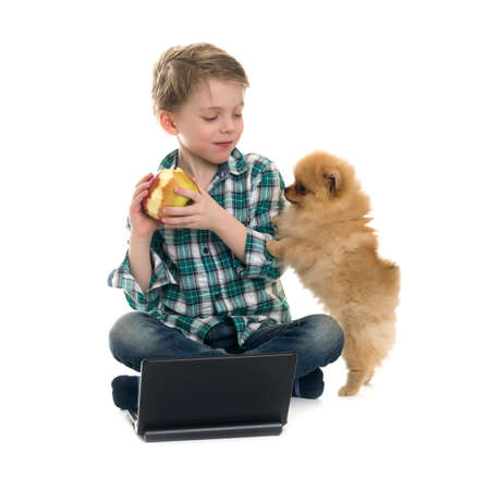 The boy with a laptop and a puppy on a white background Stock Photo - 18200455
