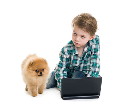 The boy with a laptop and a puppy on a white background Stock Photo - 18200490