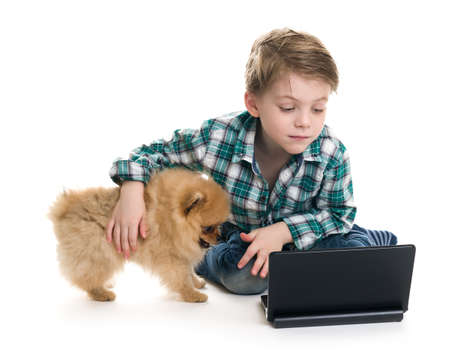 The boy with a laptop and a puppy on a white background Stock Photo - 18200477