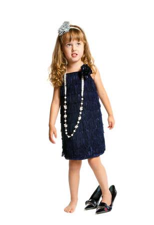 小さな女の子が、白い背景の上で踊ってレトロなドレス