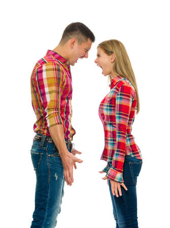 Portrait of an angry couple shouting each other head to head against white background