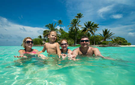 Family swims against the beautiful tropical island photo