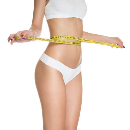 Woman measuring perfect shape of beautiful toned waist healthy isolated on white background  Perfect Slim Body  Diet photo
