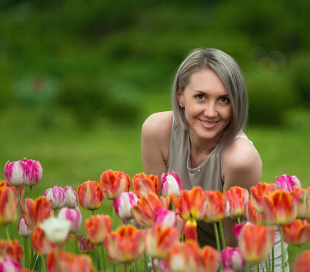 Beautiful woman on background of grass and red tulip photo