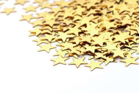 Christmas decoration of golden confetti stars against white  photo