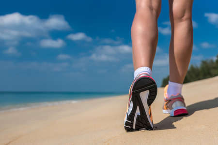 Close up of feet of a runner running in the beach training for marathon and fitness healthy lifestyle wellness concept  写真素材
