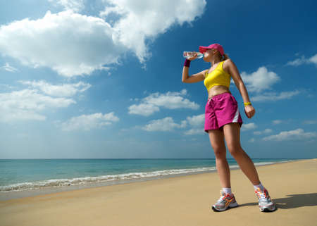 Fitness woman drinking water after running at beach  Thirsty sport runner resting taking a break with water bottle drink outside after training on the sea background photo