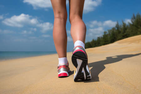 Close up of feet of a runner running in the beach training for marathon and fitness healthy lifestyle wellness concept  photo