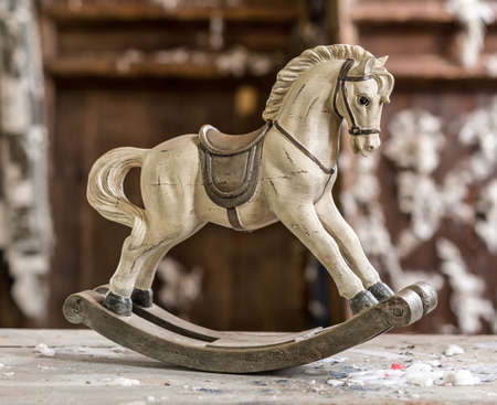 Vintage old rocking horse on a wooden background photo