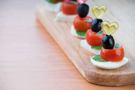 Simple snack canape with tomato, mozzarella and basil close-up on wooden background photo