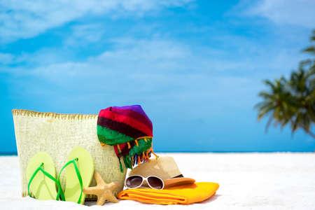 Zomer strand tas met zeester, handdoek, gezongen lasses en flip flops op zandstrand Stockfoto