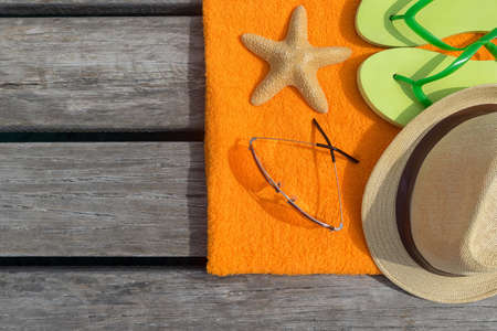 Beach slippers, towel and sunglasses on wood background  Concept of leisure and travel photo