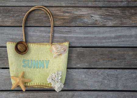 Summer beach bag with text sunny on wood background  Concept of leisure and travel photo