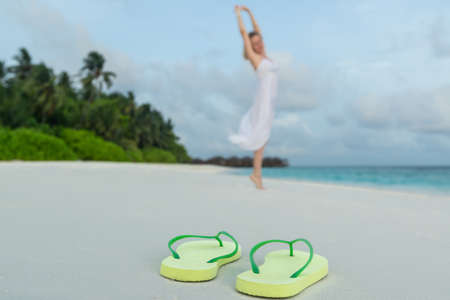woman in a white dress dancing on the tropical beach against flip flops closeup photo