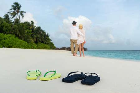 romantic couple hug on sea sand beach against male and female flip flops closeup photo