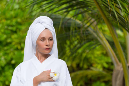 health, spa and beauty concept - beautiful woman in towel photo