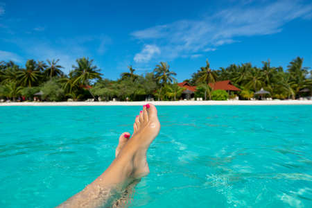 beach feet: Close-up of female foot in the blue water on the tropical beach  Vacation holidays