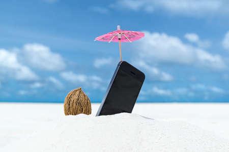 Mobiele telefoon en cocktail paraplu op het strand met de zee op de achtergrond Stockfoto - 29747241