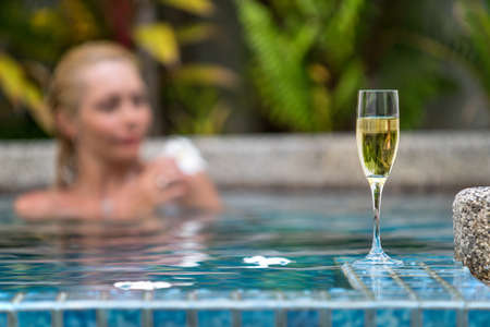 Champagne near swimming pool on a background of a beautiful woman relax Stock Photo
