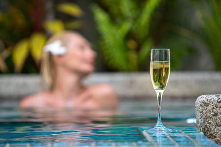 Champagne near swimming pool on a background of a beautiful woman relax photo