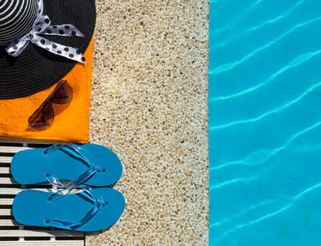 swimming shoes: Flip Flop, towel, hat on pool edge with surface of water background Stock Photo