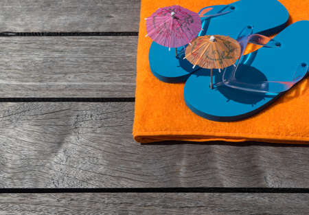 Beach slippers, towel on wood background  Concept of leisure and travel photo