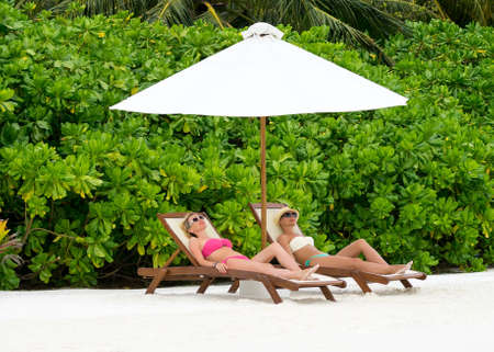 adult couple: Beautiful girls relaxing on a beach chair near the sea