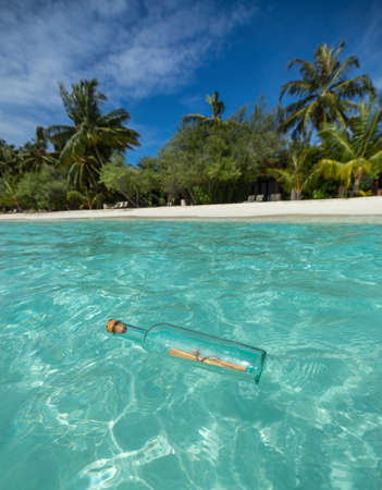ashore: Message in a bottle washed ashore on a tropical beach  Stock Photo