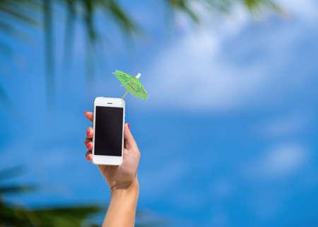 背景の空の携帯電話とカクテルの傘を示す女性手